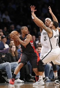Brooklyn Nets forward Paul Pierce (34) and Nets guard Deron Williams (8) defend Toronto Raptors guard Kyle Lowry, left, in the first half of an NBA basketball game, Monday, Jan. 27, 2014, in New York. (AP Photo/Kathy Willens)